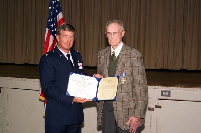 US Air Force Colonel Dana Atkins, 20th Fighter Wing Commander, Shaw Air Force Base, South Carolina, holds a certificate awarding the Distinguished Flying Cross to retired US Air Force Major Charles Bonner, a World War II B-17 pilot. MAJ Bonner received the Cross for his efforts in bringing his crippled aircraft and wounded crewmembers home to safety after a bombing mission over Germany