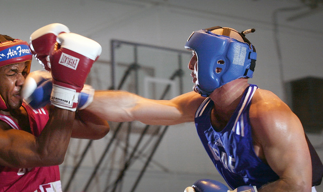 CAPT. Joseph Pastorello, right, uses his right to penetrate AIRMAN First Class Qwallion L. Busby's defenses during the 27th Annual Air Force Boxing Championships held at Kelly Air Force Base, Texas