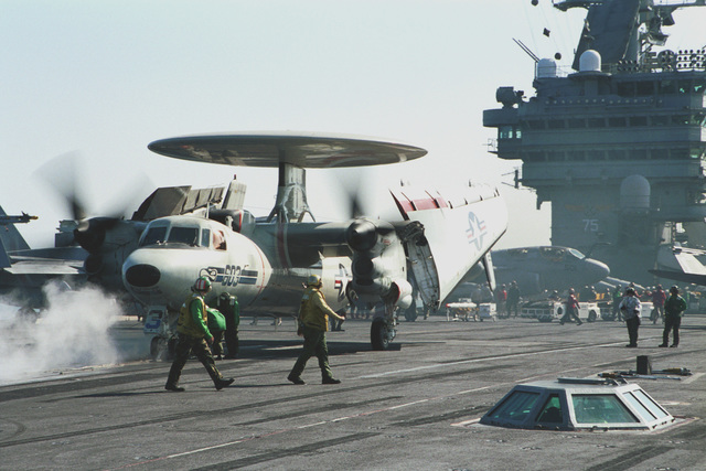 Flight deck personnel prepare an E-2 Hawkeye aircraft assigned to Carrier Airborne Early Warning Squadron One Twenty Six (VAW-126), to be launched from the flight deck of USS HARRY S. TRUMAN (CVN 75). Truman is on station in the Persian Gulf in support of Operation SOUTHERN WATCH