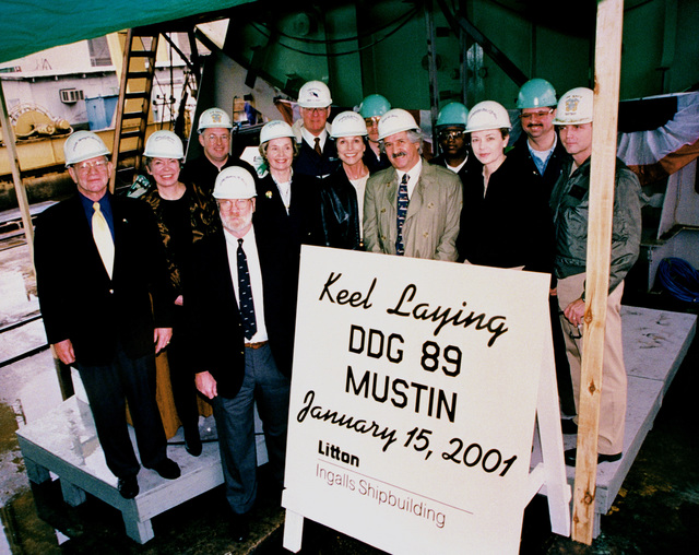The participants in the official keel laying ceremony for the Arleigh Burke class Aegis guided missile destroyer USS MUSTIN (DDG 89) pose for a photograph. They are (left to right) Row 1 Vice Admiral (VADM) Henry M. Mustin, USN (Ret) and Lieutenant Commander (LCDR) Thomas M. Mustin, USN (Ret) grandson of the ships namesake; Row 2 Jean Mustin, Ships Sponsor; Doug St. Denis, Ships Sponsor; Dale St. Denis, husband of Doug St. Denis; Commander (CDR) Ann Phillips, USN, PCO; Captain Philip Johnson, USN, Supervisor of Shipbuilding, Pascagoula; Row 3 CDR Steve Metz, Aegis Area Commander/Destroyer Projector Officer; Dave Wright, President, Ingalls Shipbuilding; Mark Broadus, welding work leaderman...