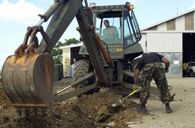 Members of the 820th Red Horse Squadron, Nellis Air Force Base, Nevada, use a backhoe to prepare the ground for construction of new Marine barracks during Operation NEW HORIZONS in Castries, Saint Lucia. Approximately 100 Marine, Army and Air Force personnel have deployed to Saint Lucia as part of New Horizons. The operation has a two fold mission of readiness and humanitarian assistance in the Caribbean and Latin America