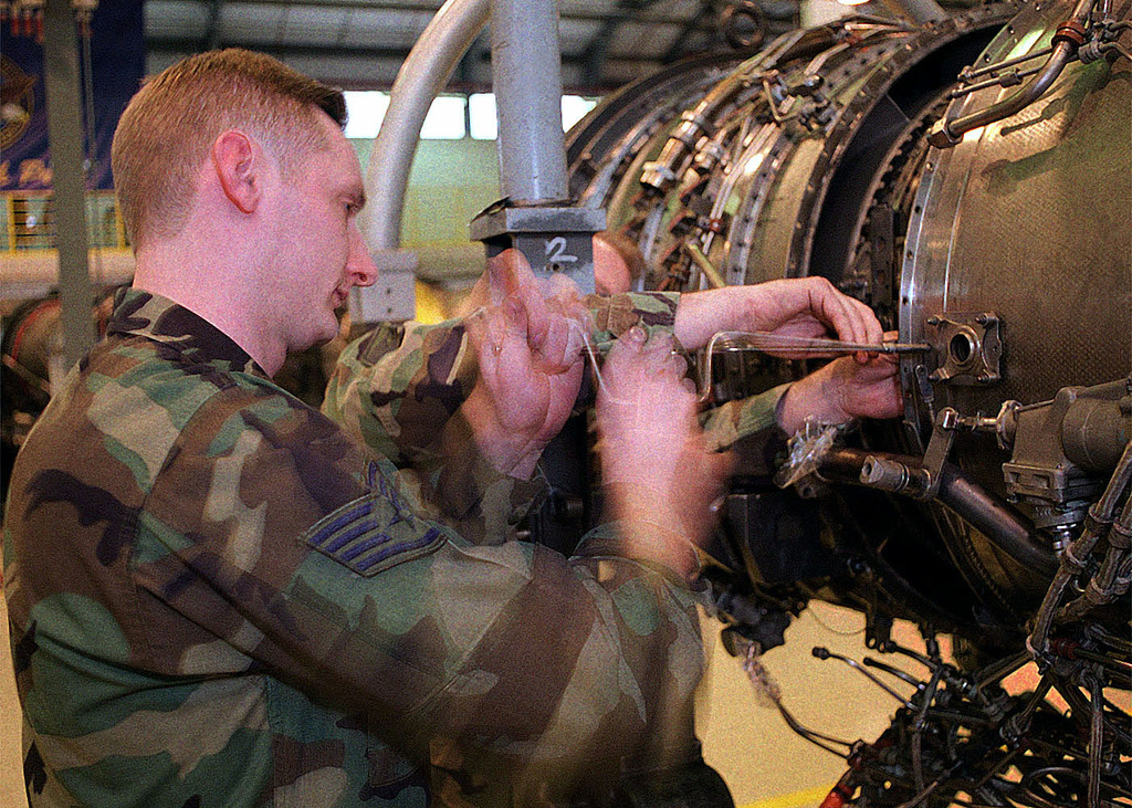US Air Force STAFF Sergeant Troy Bolt, on temporary duty to the 48th Component Repair Squadron, 48th Fighter Wing, Royal Air Force Lakenheath, United Kingdom, from the 3rd Component Repair Squadron, Elmendorf Air Force Base, Alaska, Removes hardware from the fan exit guide vanes of a Pratt and Whitney F100-PW-220 engine. (Duplicate image, see also DF-SD-01-08497 or search 010122-F-4177H-012)