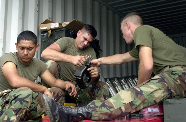US Marines from the 8th Engineer Support Battalion, 2nd Fleet Service Support, Charlie Company, sit beneath the shelter of a courier van while repairing a damaged jackhammer. Approximately 100 marines, soldiers and airmen have deployed to Saint Lucia as part of Exercise NEW HORIZONS. New Horizons has a two fold mission of readiness training and humanitarian assistance in the Caribbean and Latin America