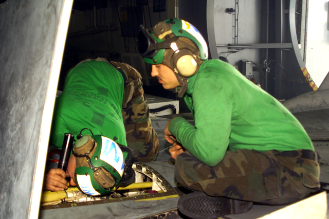 US Navy Aviation Structural Mechanic John Judson watches US Navy Aviation Structural Mechanic First Class David Yelverton rig a wing switch on a F-14 Tomcat aircraft, assigned to Fighter Squadron Thirty-Two (VF-32) aboard USS HARRY S. TRUMAN (CVN 75). Truman is on station in the Persian Gulf in support of Operation SOUTHERN WATCH