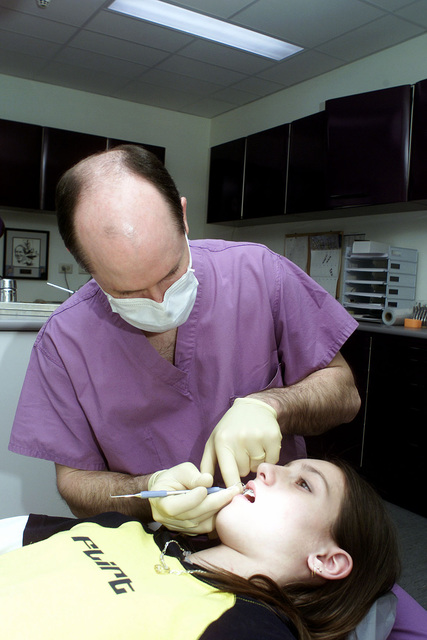 US Air Force Lieutenant Colonel, Dr Drew Fallis, Orthodontist, 52nd Dental Squadron, Spangdahlem Air Base, Germany, performs an arch wire adjustment procedure on 12-year-old Rachael Martini, at the Bitburg dental clinic