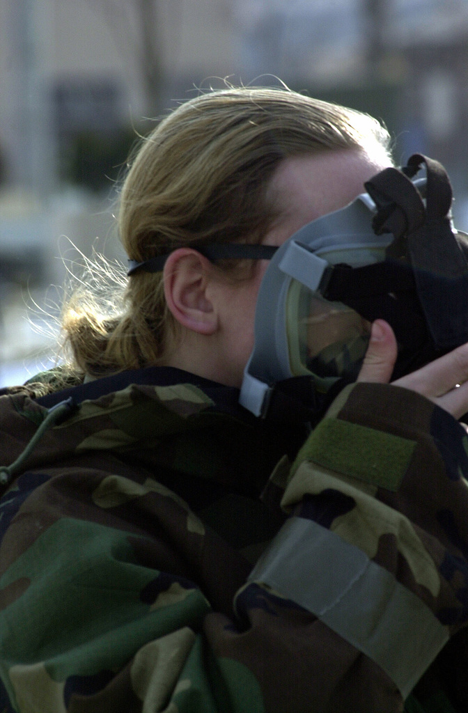 US Air Force AIRMAN Sherry Petras, 51st Security Forces Squadron, shows the second step in donning an MCU-2A/P protective mask, placing the mask over your face, during Osan Air Base, Republic of Korea's IRRE/CERE (Initial Response Readiness Exercise/ Combat Employment Readiness Exercise)
