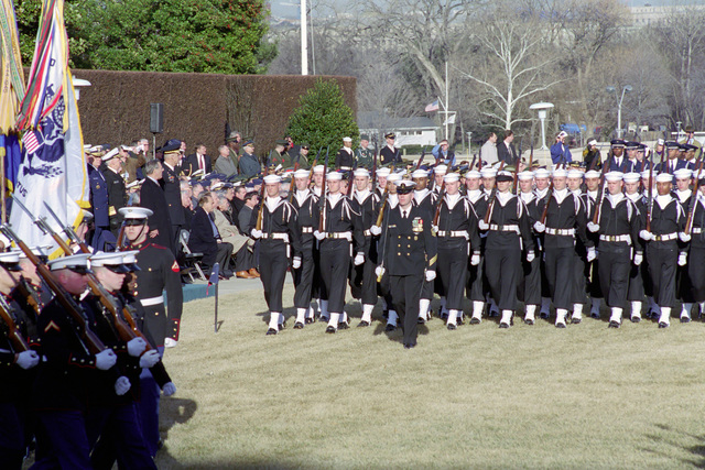 The Honorable Donald H. Rumsfeld (left, center), U.S. Secretary of Defense (SECDEF), watches as the U.S. Marine Corps (left), the U.S. Navy (center) and the U.S. Air Force (rear), Joint Services Honor Guard, pass in the Armed Forces Welcoming Ceremony held on the River Entrance Parade Field, the Pentagon, Washington, D.C., Jan. 26, 2001, following his Oath of Office Ceremony at the White House.  OSD Package No. 010126-D-9880W-0013 to 0030 (PHOTO by Robert D. Ward) (Released)