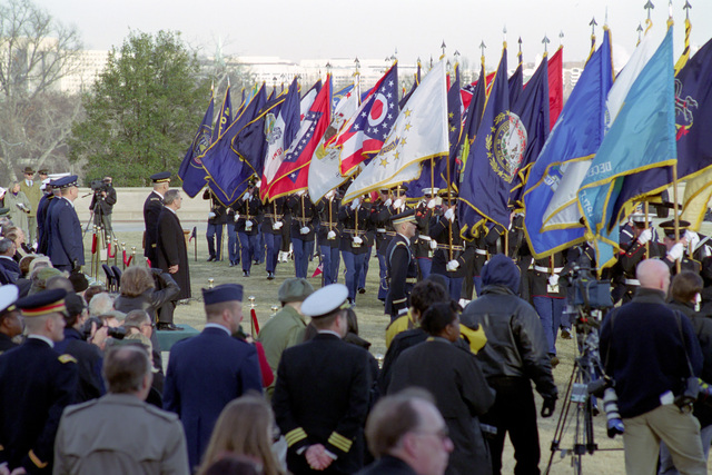 The Honorable Donald H. Rumsfeld (left, standing), U.S. Secretary of Defense (SECDEF), watches as the Colors representing the United States and its territories pass in the Armed Forces Welcoming Ceremony held on the River Entrance Parade Field, the Pentagon, Washington, D.C., Jan. 26, 2001, following his Oath of Office Ceremony at the White House.  OSD Package No. 010126-D-9880W-0013 to 0030 (PHOTO by Robert D. Ward) (Released)