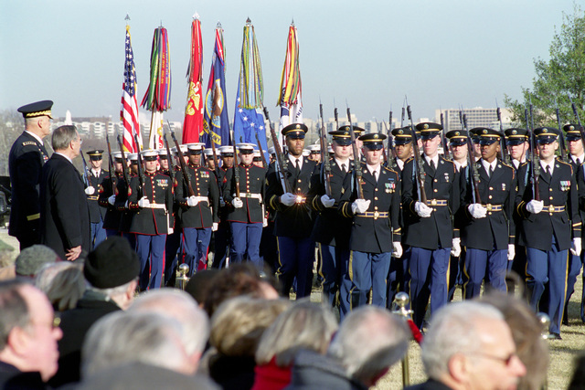 The Honorable Donald H. Rumsfeld (left, standing), U.S. Secretary of Defense (SECDEF), watches as the U.S. Army (front) and U.S. Marine Corps, Joint Services Honor Guard, pass in the Armed Forces Welcoming Ceremony held on the River Entrance Parade Field, the Pentagon, Washington, D.C., Jan. 26, 2001, following his Oath of Office Ceremony at the White House.  OSD Package No. 010126-D-9880W-0013 to 0030 (PHOTO by Robert D. Ward) (Released)