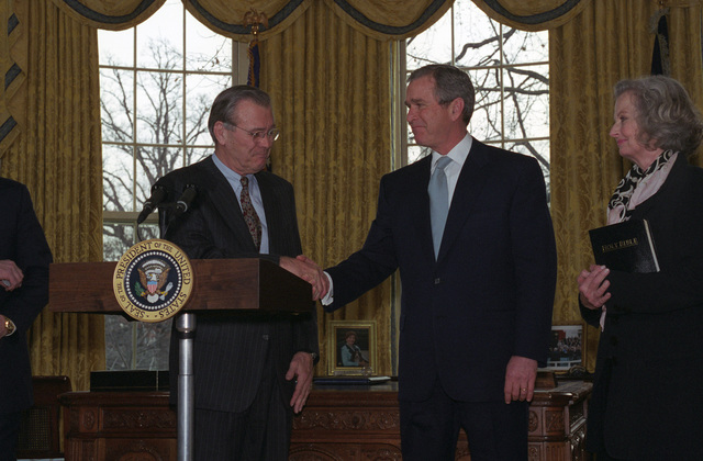 The Honorable George W. Bush (center, right), President of the United States, congratulates the Honorable Donald H. Rumsfeld (at podium), U.S. Secretary of Defense, during his Oath of Office Ceremony at the Oval Office of the White House, Washington, D.C., Jan. 26, 2001.  Mrs. Joyce Rumsfeld (right), is also present.  OSD Package No. 010126-D-9880W-001-012 (PHOTO by Robert D. Ward) (Released)