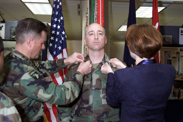 Commanding General US Army (USA) Forces Command General John W. Hendrix and Mrs. Brenda Rankin, wife of Command Sergeant Major (CSM) John C. Rankin pin the CSM rank insignia on her husband during the Frocking Ceremony for Regimental Command Sergeant Major of the Chaplain Corps, its highest Non-Commissioned Officer (NCO) position