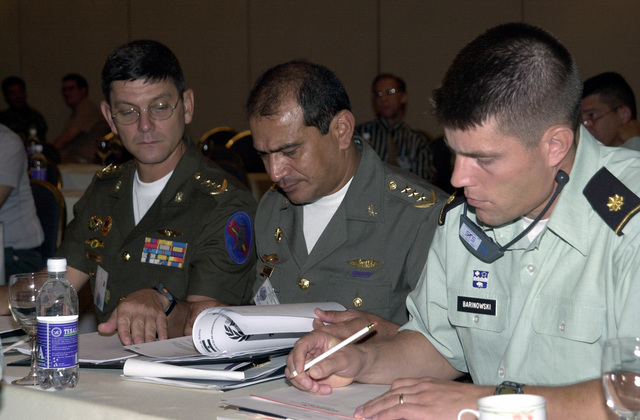 Venezuela Colonel (COL) Enrique De La Concha, left, looks over an operations order for PEACEKEEPING OPERATIONS (PKO) SOUTH-01 with Venezuela COL Jose Rodriguez at the exercise Mid-Planning Conference at the Swiss Hotel in Quito, Ecuador. On the right is Major Robert Barinowski, US Army Military Group, Venezuela. The conference is sponsored by US Southern Command in Miami, Florida, and executed by US Army South in Fort Buchanan, Puerto Rico