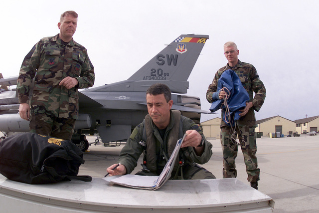 US Air Force Colonel Michael Ely reviews the maintenance forms for an F-16CJ, visible in the background, before accepting the aircraft from US Air Force CHIEF MASTER Sergeant Carey Castle (left) and US Air Force AIRMAN First Class Nathan Castle (right) for a training flight from Shaw Air Force Base, South Carolina. The father/son team are both F-16 Fighting Falcon Crewchiefs and had the opportunity to launch COL Ely's jet together as a team before CMSGT Castle retires. The tail of the aircraft is adorned with COL Ely's Commanders markings as he is the Commander of the 20th Operations Group