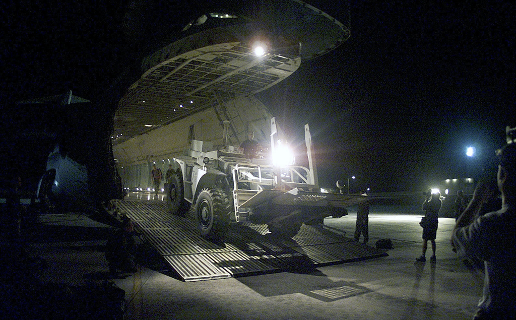 """A forklift intended for the Indian earthquake relief effort is unloaded from a Dover Air Force Base, C-5B """"Galaxy"""" aircraft. Cargo composed of tents, blankets and sleeping bags, along with heavy equipment is bound for Ahmedabad International Airport, India"""
