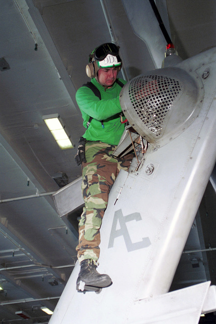 """Aviation Ordnanceman Third Class Matthew Burcham touches up the paint to prevent corrosion to the rivets located on the tail wing of a SH-60F Helicopter assigned to Anitsubmarine Warfare Squadron Seven (HS-7) """"Dusty Dogs"""". The squadron is currently embarked on board USS Harry S. Truman (CVN 75). TRUMAN is on station in the Arabian Gulf in support of Operation SOUTHERN WATCH (OSW). OSW is the mission that enforces the coalition imposed southern """"no-fly zone"""" over Iraq"""