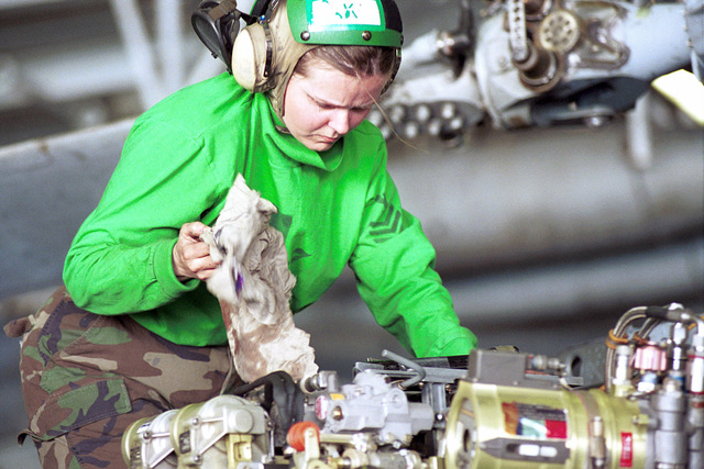 """Aviation Structural Mechanic First Class Amy Leach assigned to Antisubmarine Helicopter Squadron Seven (HS-7) """"Dusty Dogs"""", performs routine maintenance on the rotors of a SH-60F helicopter in the hangar bay of USS Harry S. Truman (CVN 75). TRUMAN is on station in the Arabian Gulf in support of Operation SOUTHERN WATCH (OSW). OSW is the mission that enforces the coalition imposed southern """"no-fly zone"""" over Iraq. (Duplicate image, also see DN-SD-02-04088 or 010202-N-2510L-004)"""