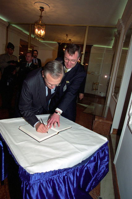 The Honorable Donald H. Rumsfeld (left), U.S. Secretary of Defense (SECDEF), signs the guestbook of the hotel at the 37th Munich Conference on Security Policy in Munich, Germany, Feb. 3, 2001.  OSD Package 010203-D-2987S-001-030 (PHOTO by Helene C. Stikkel) (Released)
