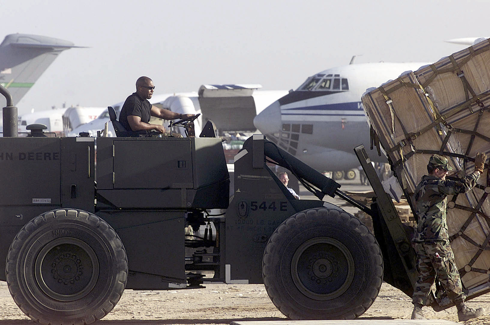 United States Air Force personnel assigned to the 633rd Air Mobility Support Squadron, use a John Deere 544E Forklift to move a pallet of humanitarian earthquake relief supplies bound for the earthquake stricken area in India