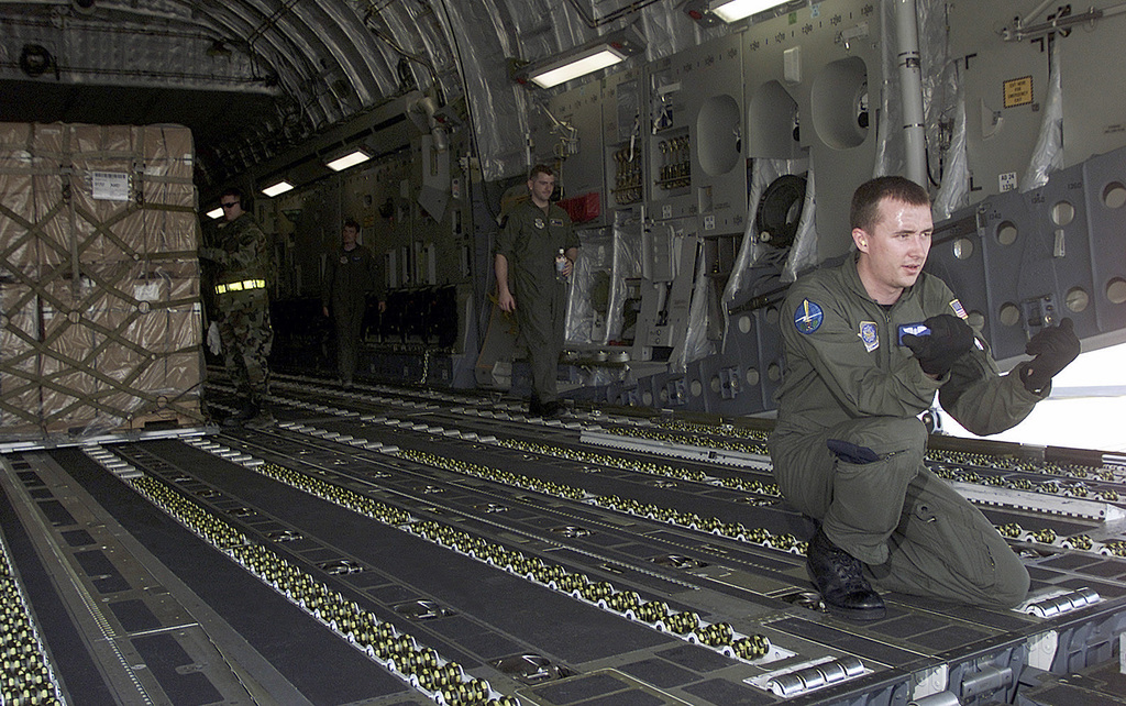 United States Air Force STAFF Sergeant Rich DeLucia directs a forklift to unload a pallet of humanitarian earthquake relief supplies, after arriving at Ahmedabad International Airport