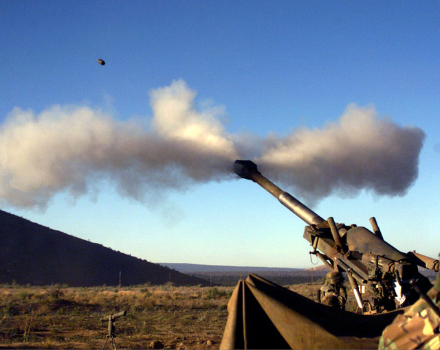 A round from an M-198 Howitzer from 1ST Battalion, 12th Marines, blasts over a dormant steam vent in the Pohakuloa Training Area, Hawaii, during a Hawaiian Combined Arms Operation