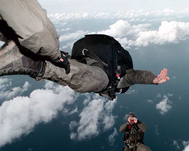 A US Navy (USN) Sailor assigned to Naval Special Warfare Unit One (NSWU1), takes a picture of the other jumpers exiting the ramp of helicopter during a High Altitude Low Opening (HALO) jump over Orote Point, Santa Rita, Guam