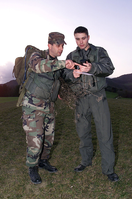 "US Air Force STAFF Sergeant Rick Sapone (left) and US Air Force Second Lieutenant Adam Cuquet (right), 31st Fighter Wing, Aviano Air Base, Italy, read coordinates off their global positioning satellite device in their roles as ""survivors"" during a joint NATO search and rescue exercise with the 83rd Search and Rescue Squadron, Italian Air Force, in Rimini, Italy. The mission allows the two countries to put into practice procedures that will maintain search and rescue proficiency"