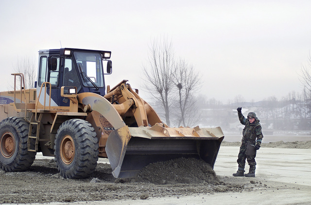STAFF Sergeant Jason Rowe, 51st Civil Engineering Squadron, Osan Air Base, directs a Samsung front-loader over to a bomb crater with clean fill