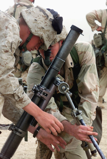 US Marine Corps (USMC) Corporal (CPL) Jesse Kelly and USMC Private First Class (PFC) Eugune, 7th Marines Weapons Company-Alpha Co 1ST Battalion, 7th Marines (1/7) practice setting up an M224 60mm Lightweight Mortar system during Operation ENDURING FREEDOM at Camp Coyote, Kuwait