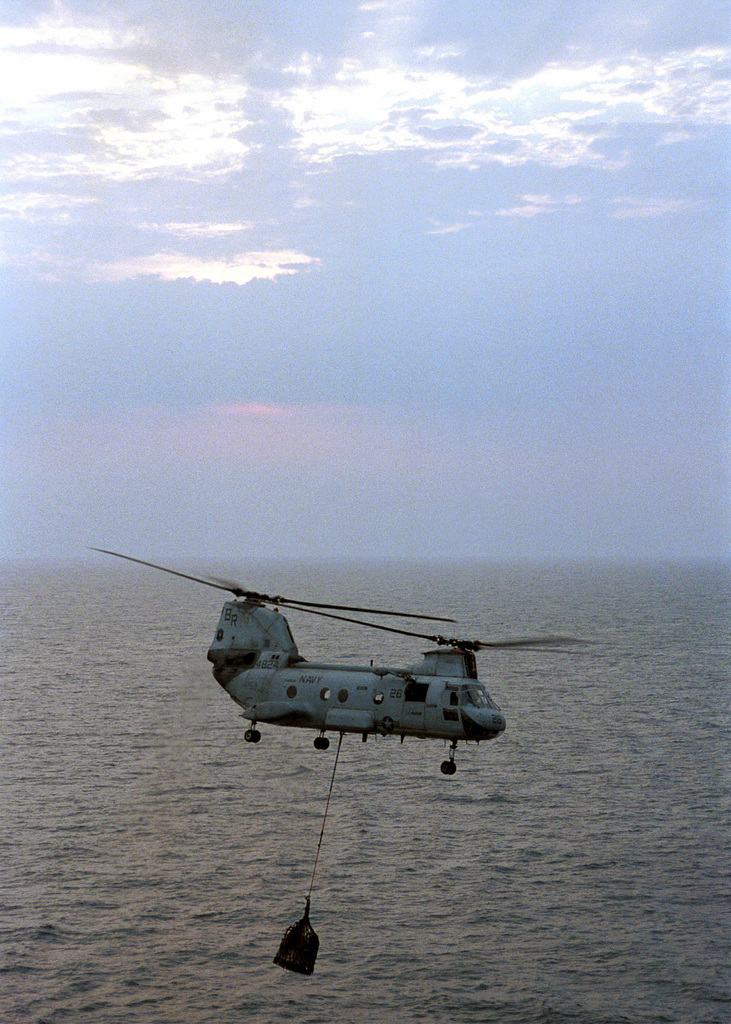 """A CH-46D Sea Knight carries stores to the flight deck of USS Harry S. Truman (CVN 75) during a vertical replenishment with USNS Kanawha (T-AO 96). TRUMAN is on station in the Arabian Gulf in support of Operation SOUTHERN WATCH (OSW). OSW is the mission that enforces the coalition imposed southern """"no-fly zone"""" over Iraq"""