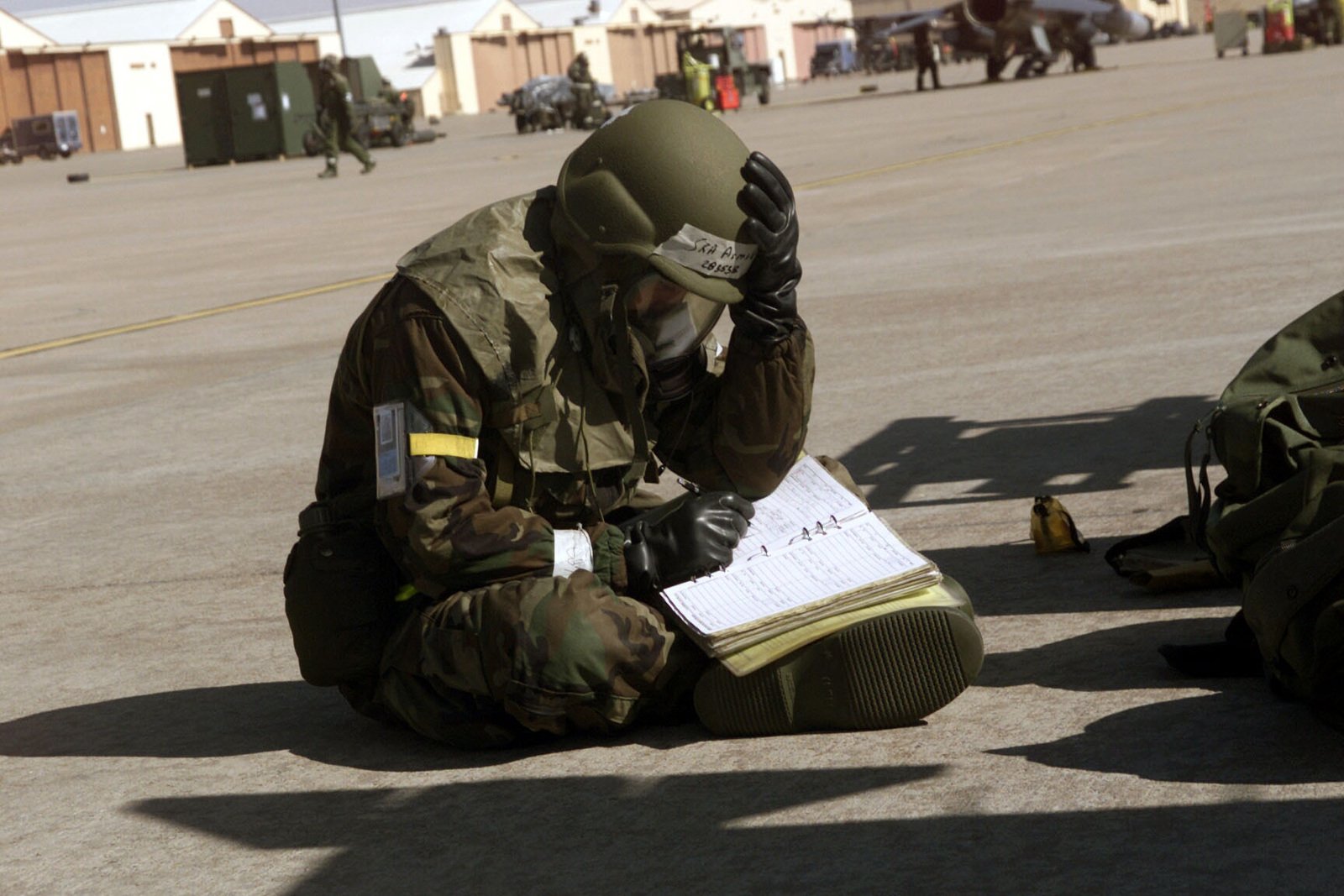 US Air Force AIRMAN First Class Chad Armold makes entry in his log book, while wearing Mission-Oriented Protective Posture response level 4 (MOPP-4) gear at Cannon Air Force Base, New Mexico