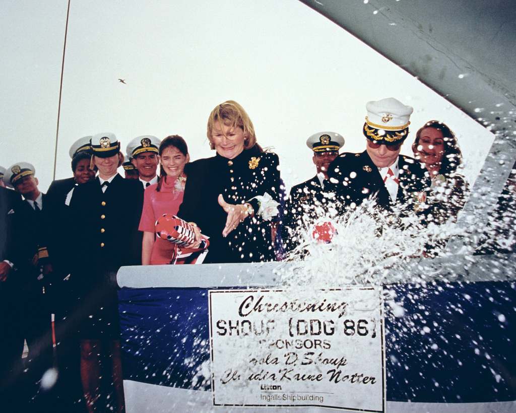 Ms Claudia Kaine Natter, (left), Ships Sponsor and Lieutenant Colonel (LCOL) Catherine Chase, USMC, Matron of Honor, both break the traditional bottles of champagne over the brow of the guided missile destroyer USS SHOUP (DDG 86) at the conclusion of the vessels christening ceremony at the Ingalls Shipyard