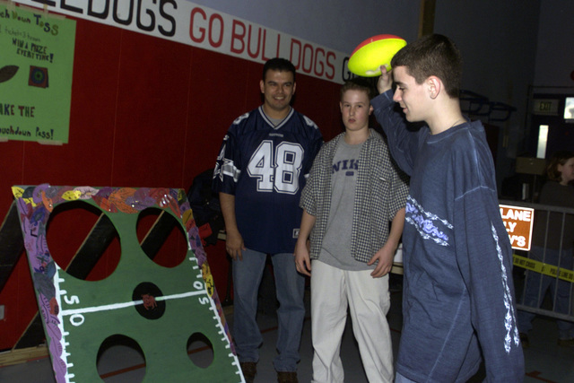 """Tyson Cickels a 12-year old student at Spangdahlem Middle School """"The BullDogs"""", Spangdahlem AB, Germany plays the """"touch down toss"""" game at the BullDogs Count Fair"""