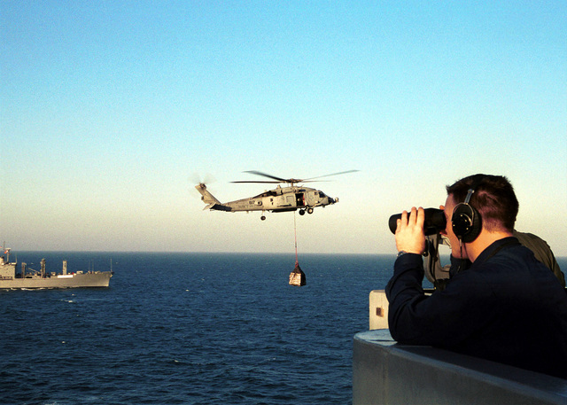 A US Navy Boatswain's Mate uses binoculars to keep a watchful eye on an SH-53F helicopter from Antisubmarine Squadron Seven (HS-7) as it carries stores from USNS KANAWHA (T-AO 96) to the flight deck of USS HARRY S. TRUMAN (CVN 75) during a vertical replenishment at sea. Truman is on station in the Persian Gulf in support of Operation SOUTHERN WATCH