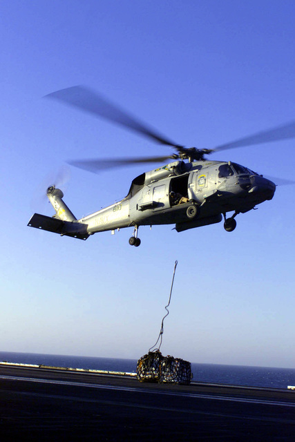 An SH-60 Helicopter from Anti-Submarine Squadron Seven (HS-7) drops a load of supplies during a Vertical Replinishment (VERTREP) on board USS HARRY S. TRUMAN (CVN 75). Truman is on station in the Persian Gulf in support of Operation SOUTHERN WATCH