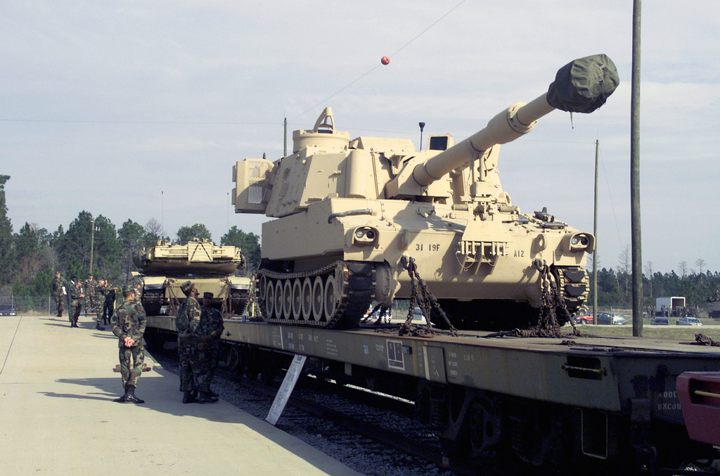 """US Army soldiers inspect a M109A6 155mm """"Paladin"""" Self Propelled Howitzer from the 1ST Battalion, 9th Field Artillery, 3rd Infantry Division (Mechanized), loaded aboard a railroad flat car at Fort Stewart, GA"""