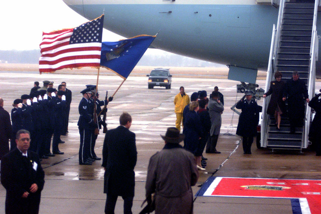 The Langley Air Force Base, Virginia, Honor Guard hoist the colors up high as US President George W. Bush and the first lady, Mrs. Laura Bush, come down the steps of Air Force One