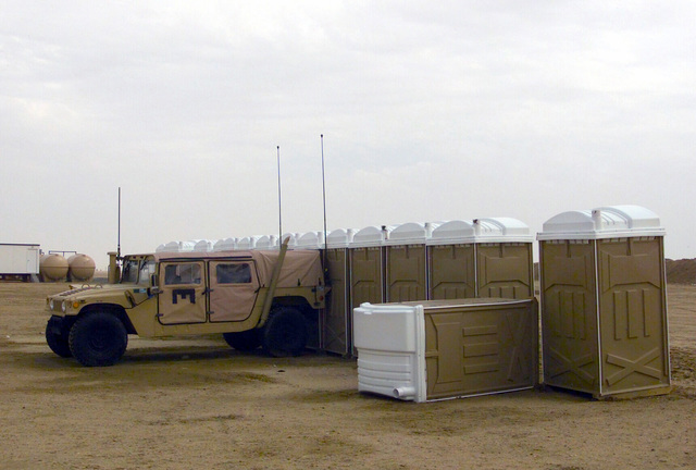 A US Marine Corps (USMC) M998 High-Mobility Multi Purpose Vehicle (HMMWV) is used to support line of portable restrooms due to intense winds at Camp Coyote, Kuwait, during Operation ENDURING FREEDOM