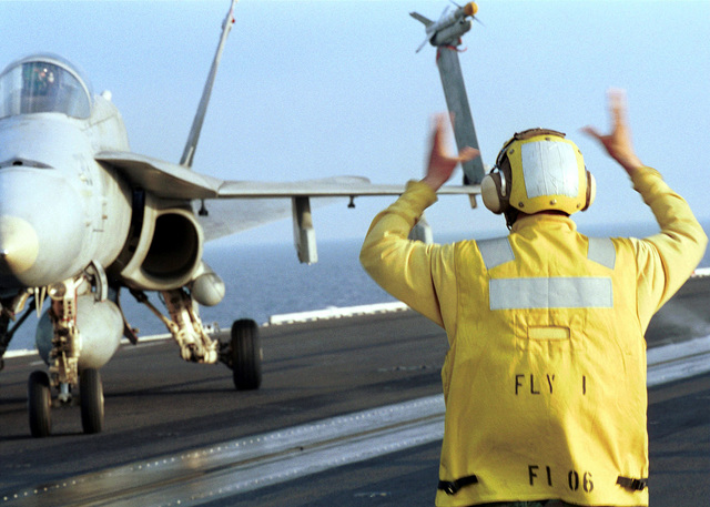 US Navy Aviation Boatswain's Mate (Handler) AIRMAN Ethan Lane parks an F/A-18 Hornet aircraft from Strike Fighter Squadron Thirty-Seven (VFA-37) on the reverse four row on the bow of the flight deck of USS HARRY S. TRUMAN (CVN 75). Truman is on station in the Persian Gulf in support of Operation SOUTHERN WATCH
