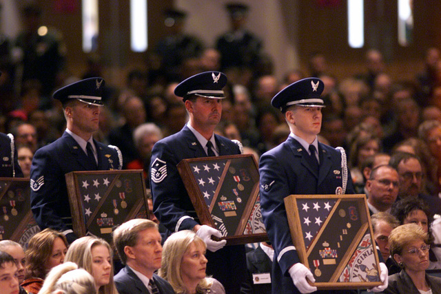 Air Force Honor Guard members carry shadow box's that will be placed at the pictures of the 18 Virginia Air National Guard and three Florida Army National Guard members who were killed on a March 3rd in an C-23 Sherpa plane crash in Unadilla, Georgia. The memorial service, which took place at Rock Church, Virginia Beach, Virginia, was attended by Deputy Secretary of Defense, Paul D. Wolfowitz (not shown) and various other civilian and military dignitaries and over 4000 members of the community. The 18 airmen were assigned to the 203rd Red Horse Flight at Camp Pendleton State Military Reservation in Virginia Beach, Virginia and were returning from temporary duty at Hurlburt Field, Florida...