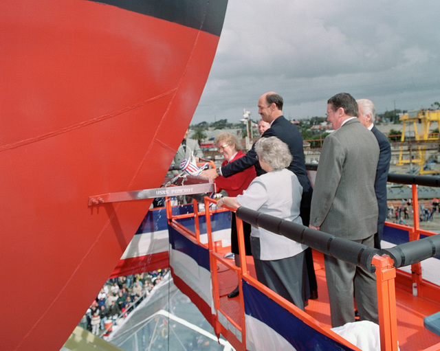 As member of the christening party look on, Mrs. Arlene May Pomeroy Castle, ships sponsor, breaks the traditional bottle of champagne over the bow of the Military Sealift Command (MSC), strategic heavy lift ship USNS POMEROY (T-AKR 316) to officially launch the ship