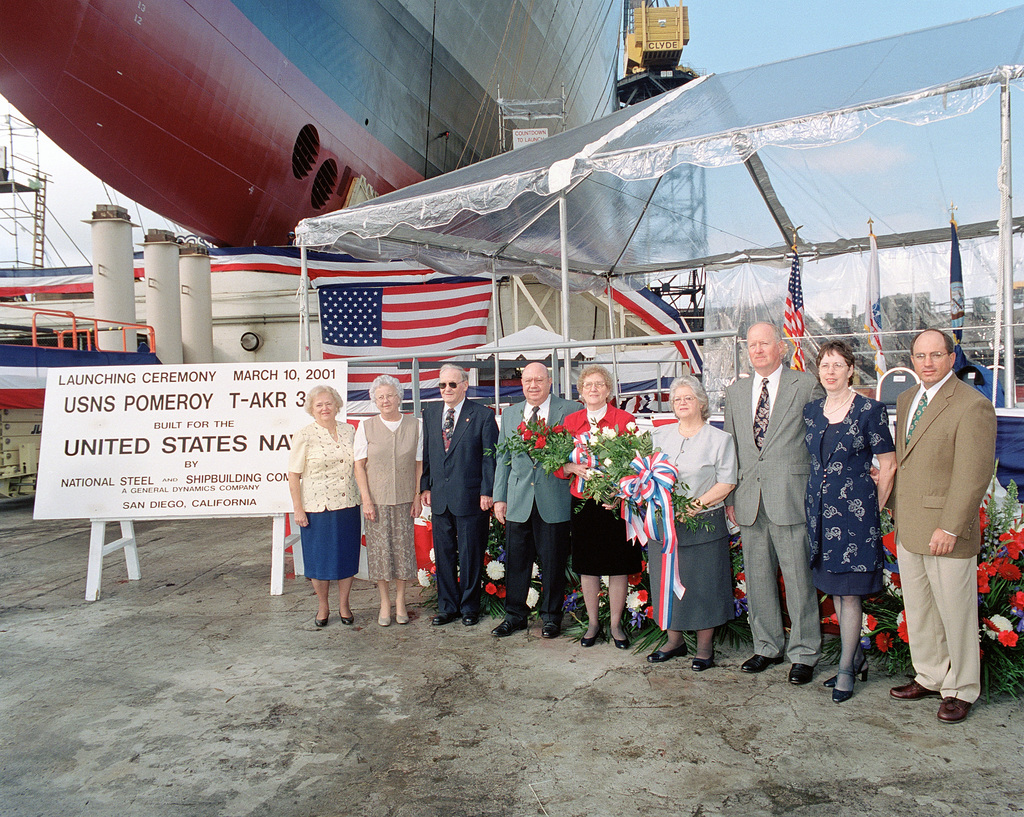 Family members pose for a photograph with the ships sponsor, Mrs. Arlene May Pomeroy Castle and the ships maid of honor, Ms Nancy Pomeroy under the bow of the Military Sealift Command (MSC) strategic heavy lift ship USNS POMEROY (T-AKR 316) just prior to the vessels christening and launch