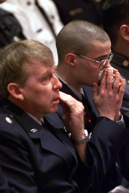 Two men mourn the loss of 18 Virginia Air National Guard and three Florida Army National Guard members killed in a March 3rd C-23 Sherpa plane crash in Unadilla, Georgia, pay tribute to the men at a memorial service in Virginia Beach, Virginia. The memorial, which took place at Rock Church, was attended by Deputy Secretary of Defense, Paul D. Wolfowitz (not shown) and various other civilian and military dignitaries and over 4000 members of the community. The 18 airmen were assigned to the 203rd Red Horse Flight at Camp Pendleton State Military Reservation in Virginia Beach, Virginia and were returning from temporary duty at Hurlburt Field, Florida. The three soldiers were assigned to the ...