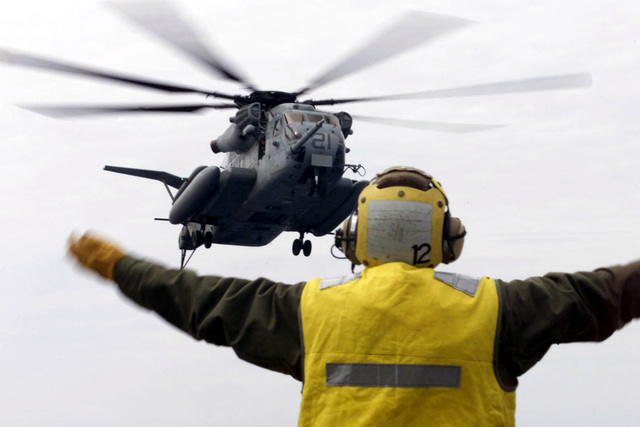 Aviation Boatswain's Mate 3rd Class Christopher Halcomb directs the landing of a CH-53 E Sea Stallion helicopter on the flight deck of USS Essex (LHD 2) for Deck Landing Qualifications (DLQs) during Blue-Green Workups. Testing their rapid response, Blue-Green Workups are a series of training exercises designed to solidify the working relationship of Sailors and Marines during an Amphibious Ready Group deployment