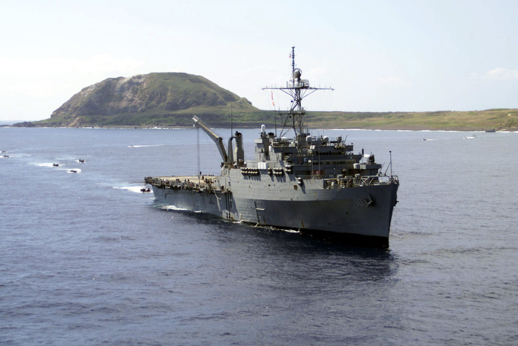 Mount Suribachi, a volcanic crater on the small island of Iwo Jima, serves as the background for USS Juneau (LPD 10) as she prepares to take on AAVs from the 31st Marine Expeditionary Unit during Blue-Green Workups off the coast of Iwo Jima on March 15, 2001. JUNEAU, which is part of the Essex Amphibious Ready Group, is off the coast to participate in the 56th Iwo Jima Commemoration. Blue-Green Workups are a series of training exercises designed to solidify the working relationship of Sailors and Marines during an Amphibious Ready Group deployment