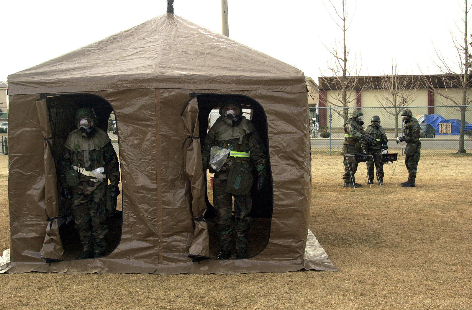 US Air Force Airmen of the 8th Fighter Wing, Kunsan Air Base, Republic of Korea, wear Mission-Oriented Protective Posture response level 4 (MOPP-4) gear as they exit the rinse off tent, the first stop of the Personnel Decontamination Stations (PDS) set up to decontaminate personnel after a simulated chemical weapons attack. During a recent Operational Readiness Inspection (ORI) airmen from Kunsan were tested on their war fighting skills