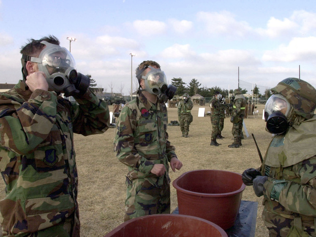 US Air Force STAFF Sergeant Brian Gracey and AIRMAN First Class Scott Bachand, members of the 8th Communications Squadron, 8th Fighter Wing, Kunsan Air Base, Republic of Korea, prepare to takeoff their MCU-2P gas mask at one of the Personnel Decontamination Station (PDS) inside the Contaminant Control Area during Kunsan's Operational Readiness Inspection. The 8th Fighter Wing personnel are being evaluated on their wartime capabilities during their Operational Readiness Inspection