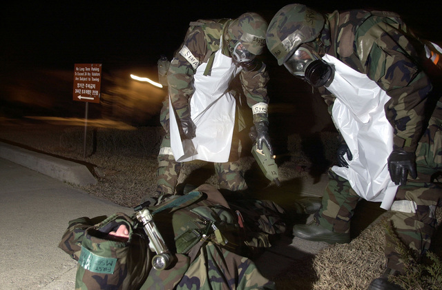 US Air Force STAFF Sergeant Martigo Caldwell, 51st Services Squadron, Osan Air Base, Republic of Korea, dressed in chemical gear, utilizes a CAMS (Chemical Agent Monitoring System) to detect chemical contamination on a simulated dead body before moving it into the morgue during Osan's Operational Readiness Inspection