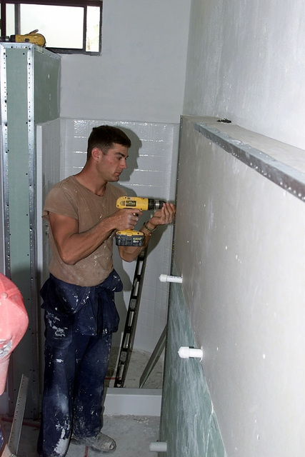 While deployed to Castries, Saint Lucia, for Exercise NEW HORIZONS, US Air Force AIRMAN Nathan Geldner, a Structural Apprentice for the 820th Red Horse Squadron, Nellis Air Force Base, Nevada, installs the corner molding for drywall for new barracks in Castries, Saint Lucia. Approximately 100 Army, Air Force, and Marine personnel are deployed to Saint Lucia as part of New Horizons. the excercise has a two fold mission of readiness training, and humanitarian assistance in the Caribbean and Latin America