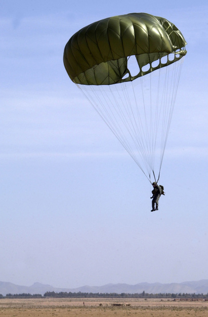 A Moroccan Army paratrooper gets ready to touch ground, during a static line parachute drop, on Ben Guerir Airfield, Morocco, part of Operation BLUE SANDS 2001