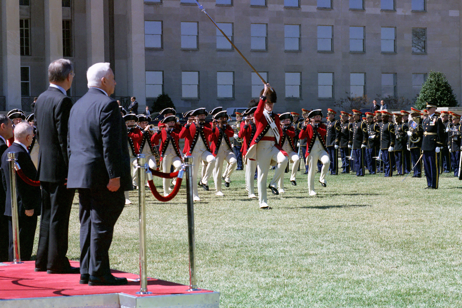 The Honorable Donald H. Rumsfeld, U.S. Secretary of Defense, stands to the left of Ariel Sharon, Israeli Prime Minister, on the reviewing stand at the River Parade Field, Pentagon, Washington, D.C., Mar. 19, 2001, as the U.S. Army's Old Guard Fife and Drum Corps marches to their front during the troop step and render honors'portion of the parade.  (DoD photo by Robert D. Ward) (Released)